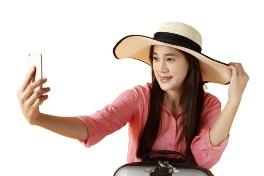 Beautiful asian woman cheerful smiling and take selfie on smart mobile phone, beauty young girl wear hat enjoy and fun in vacation isolated on white background, holiday concept. Asian women long hair wear hat shot photo by yourself with mobile phone.