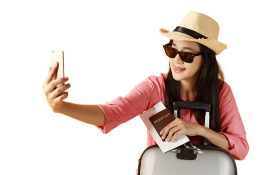 Beautiful asian woman cheerful smiling and take selfie on smart mobile phone, beauty young girl wear hat enjoy and fun in vacation isolated on white background, holiday concept.