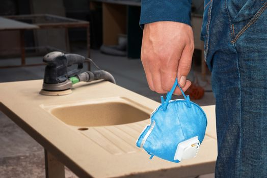 Man with respirator at work. Stone sink furniture production.