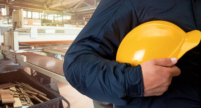 Man with yellow helmet on wooden furniture production background. Industrial cutting machine for automatic wood cutting