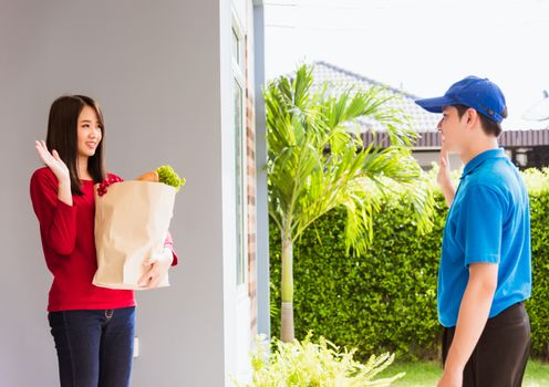 Asian young delivery man in blue uniform making grocery service giving fresh vegetables and fruits and food in paper bag to woman customer at front house after pandemic coronavirus, Back to new normal