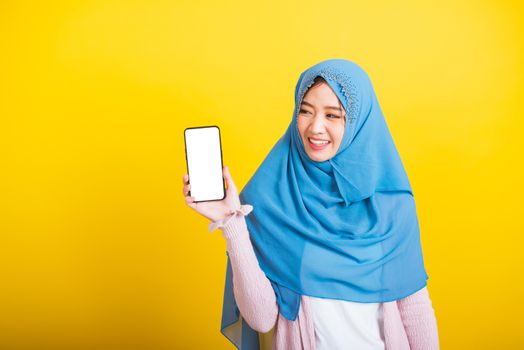 Asian Muslim Arab woman Islam wear veil hijab funny smile she talking on showing blank screen smart mobile phone, studio shot isolated on yellow background