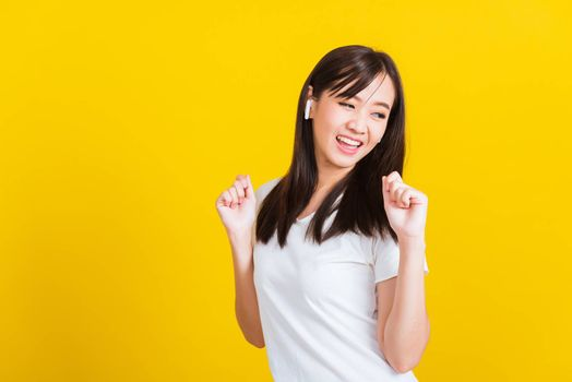 Portrait Asian of a happy beautiful young woman wear wireless earphone listening to music from smartphone having fun and dancing to sounds of favorite music studio shot isolated on yellow background