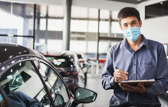 Asian saleman wear surgical mask working in inspector checking writing on clipboard in garage of dealership Wait mechanic In showroom car and insurance new normol covid-19 in showroom dealership