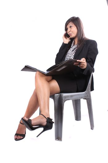 A young beautiful Indian businesswoman on phone, on white studio background.