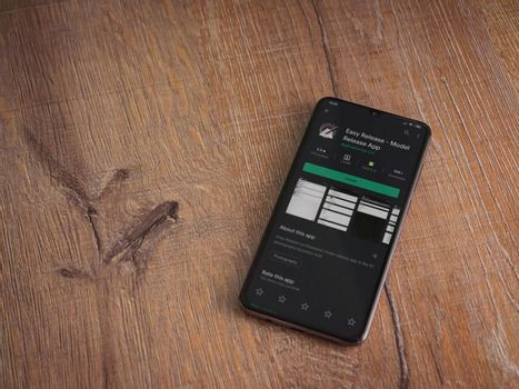Lod, Israel - July 8, 2020: Easy Release Pro - Model Release app play store page on the display of a black mobile smartphone on wooden background. Top view flat lay with copy space.