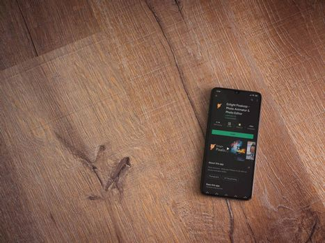 Lod, Israel - July 8, 2020: Enlight Pixaloop app play store page on the display of a black mobile smartphone on wooden background. Top view flat lay with copy space.