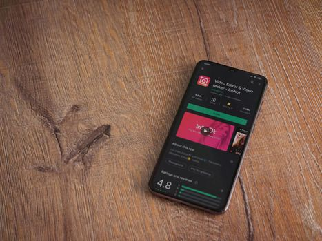 Lod, Israel - July 8, 2020: InShot - Video Editor and Movie Maker app play store page on the display of a black mobile smartphone on wooden background. Top view flat lay with copy space.