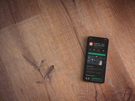 Lod, Israel - July 8, 2020: KineMaster - Video Editor and Movie Maker app play store page on the display of a black mobile smartphone on wooden background. Top view flat lay with copy space.