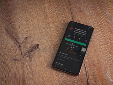 Lod, Israel - July 8, 2020: PixaMotion app play store page on the display of a black mobile smartphone on wooden background. Top view flat lay with copy space.