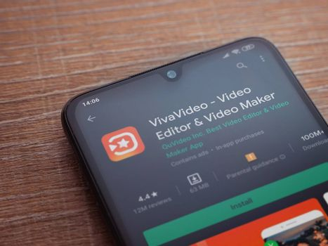 Lod, Israel - July 8, 2020: VivaVideo - Video Editor and Movie Maker app play store page on the display of a black mobile smartphone on wooden background. Top view flat lay with copy space.