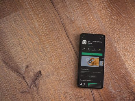 Lod, Israel - July 8, 2020: VSCO - Photo and Video Editor app play store page on the display of a black mobile smartphone on wooden background. Top view flat lay with copy space.