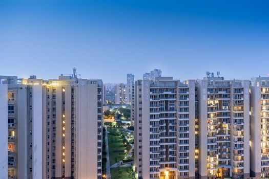 Aerial dusk shot of buuldings with warm orange lights shining out of the newly constructed homes offices and residences