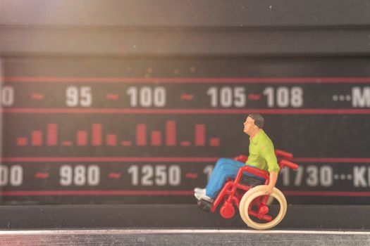 Miniature people : Disabled man sitting in wheelchair Tuning into a radio station