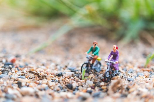 Miniature people : Travellers riding a bicycle  on The sand