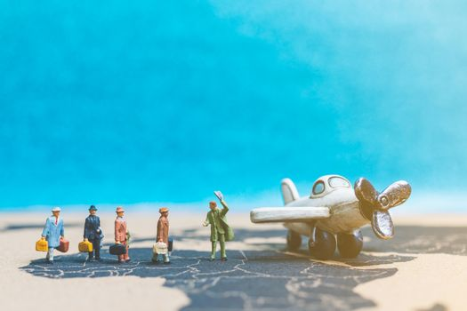 Miniature people : Travellers with airplane on The world map