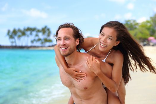 Beach fun couple happy in love piggybacking in Hawaii destination, Smiling interracial people, boyfriend carrying Asian girlfriend, young lovers on summer travel hawaiian vacation.