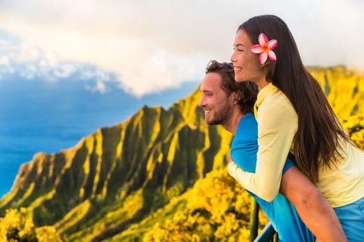 Travel couple fun piggyback at Na Pali Kauai Hawaii vacation adventure. Happy young Asian woman and Caucasian man piggybacking at nature lookout in mountains sunset. Love honeymoon vacations.
