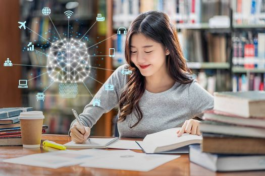 Polygonal brain shape of an artificial intelligence with various icon of smart city Internet of Things Technology over Asian young Student in casual suit reading the book in library of university