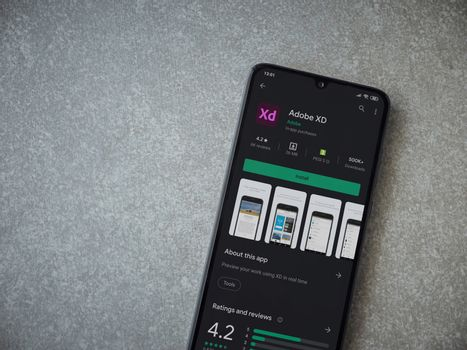 Lod, Israel - July 8, 2020: Adobe XD app play store page on the display of a black mobile smartphone on ceramic stone background. Top view flat lay with copy space.