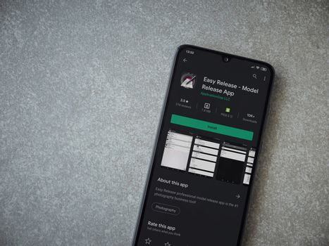 Lod, Israel - July 8, 2020: Easy Release Pro - Model Release app play store page on the display of a black mobile smartphone on ceramic stone background. Top view flat lay with copy space.