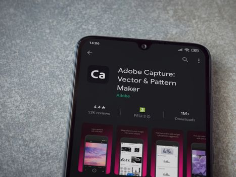 Lod, Israel - July 8, 2020: Adobe Capture - Vector and Pattern Maker app play store page on the display of a black mobile smartphone on ceramic stone background. Top view flat lay with copy space.