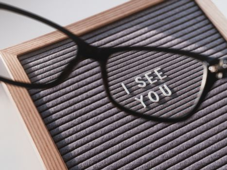 Letterboard with words I SEE YOU through eyeglasses. Closer look
