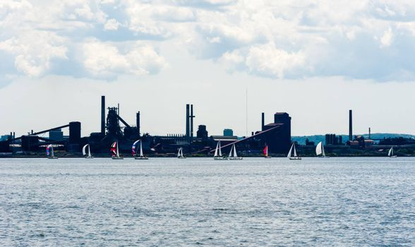HAMILTON, CANADA - JULY 03, 2016: Sailboats fly colorful spinnaker sails while passing by the industrial area of Hamilton Harbour.