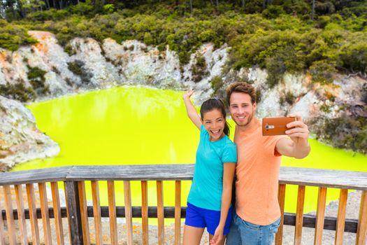 New Zealand tourist attraction couple tourists taking selfie travel destination, Waiotapu. Active geothermal green pond, Rotorua, north island, Wai-O-Tapu, New Zealand.
