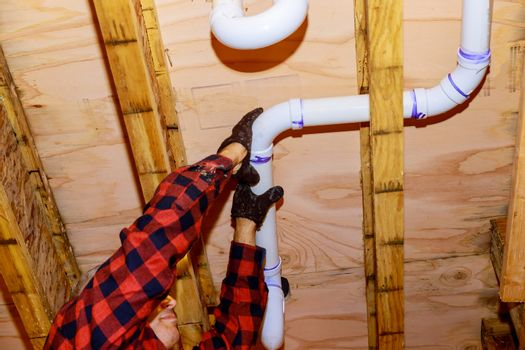 Workers are sewer toilet pipes with PVC joints allows the split to the make PVC pipe coming out the other side of the building.