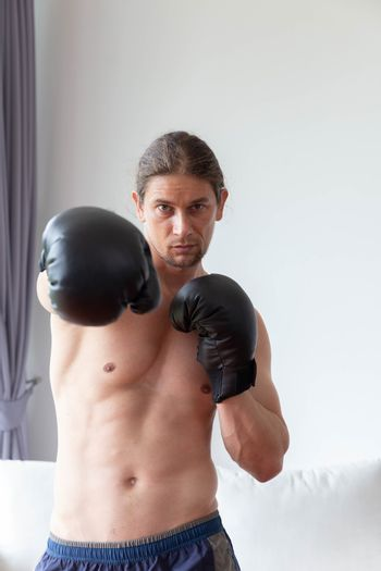An asian man has boxing training in his living room at home