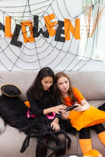 Happy Halloween by two sisters playing video game in carnival costume in decorated house