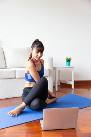 Young asian woman exercising at home in a living room with computer notebook