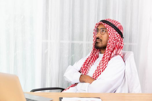Arabian businessman is thinking about his work in his office with computer notebook
