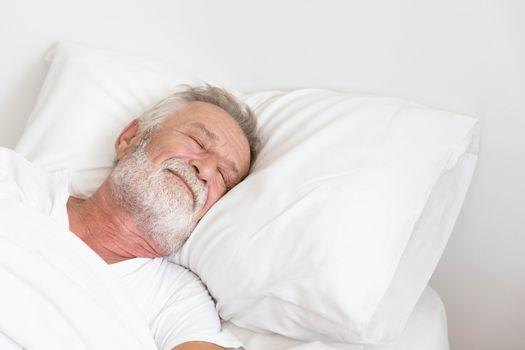 Senior retirement man sleeping happily in his white blanket bed in bedroom