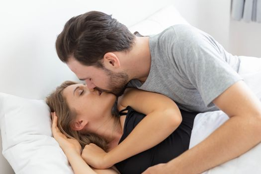 Caucasion couple kiss on bed in bedroom