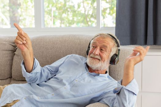 Senior retirement man listen to music using headphone feeling happy in his home