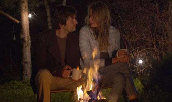 Young happy couple at night sitting near campfire. Family on weekend in the woods