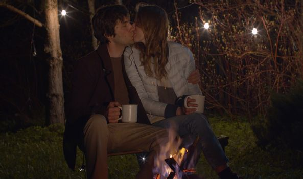 Young happy couple at night sitting near campfire and kissing. Family on weekend in the woods