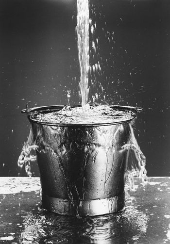 Water pouring into a bucket (b&w)