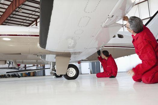 Aviation mechanics inspecting airplane wing