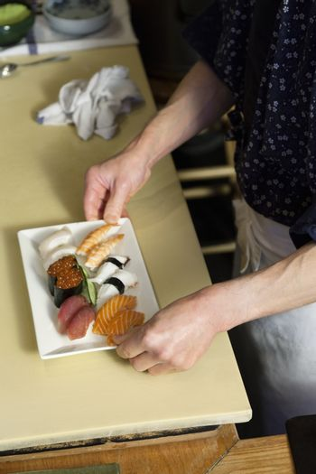 Midsection of chef holding tray of Japanese sushi in restaurant
