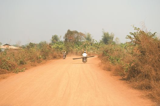 Motorcycles on rural Dirt Road in Asia