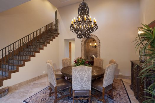 Dining room with candle chandelier in luxury mansion