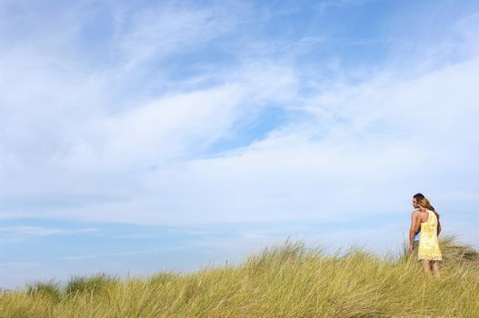 Couple Standing on grassy dune looking out to sea