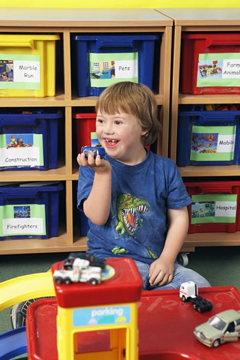 Boy (5-6) with Down syndrome playing in kindergarten