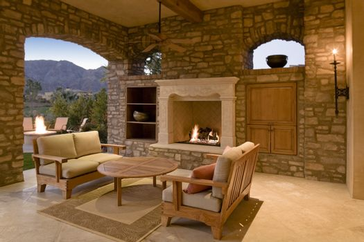 Seating furniture with fireplace in patio of mansion