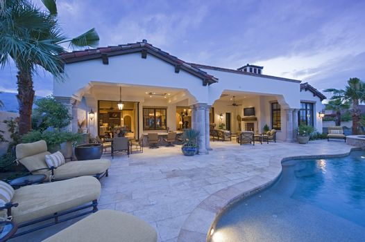 View of chaise lounges at poolside of luxury mansion