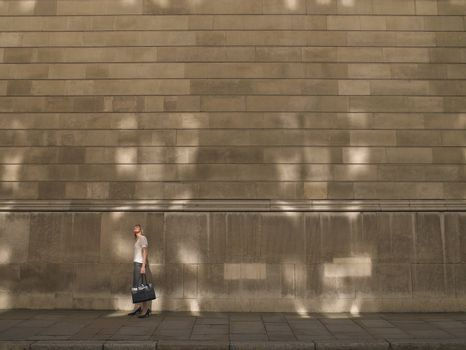 Woman standing by wall