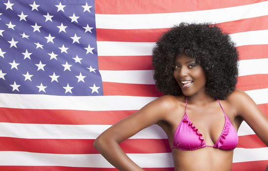 Portrait of african american woman in bikini standing against american flag